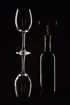 Fles wijn met een glas op een zwarte achtergrond, kurkentrekker