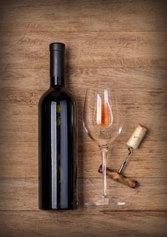 Fles wijn met glas en kurketrekker op houten