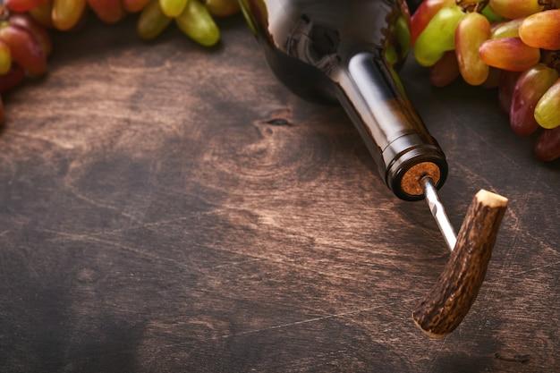 Fles wijn met kurkentrekker. een wijnfles openen met een kurkentrekker in een restaurant. wijnsamenstelling op donkere rustieke achtergrond met kopieerruimte. bespotten.