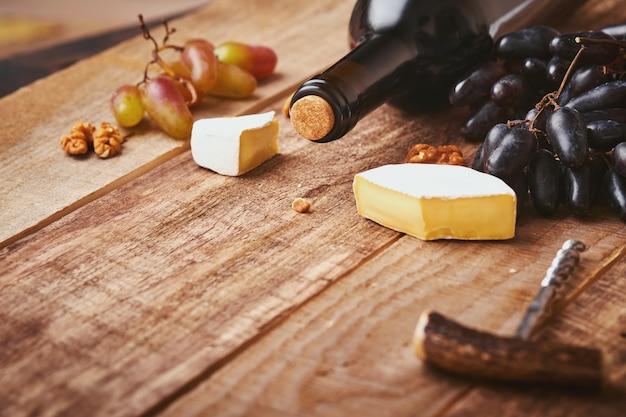 Fles wijn met kurkentrekker. met druiven, plak kaas camembert, moer op oude grijze betonnen tafel achtergrond met kopieerruimte. rode wijn met een wijnstoktak. wijnsamenstelling op rustieke achtergrond. bespotten.