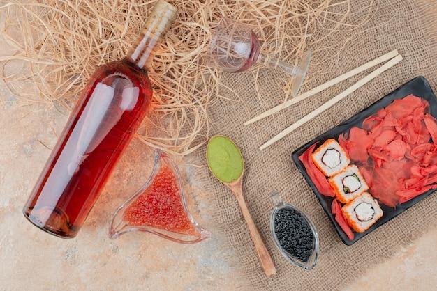 Fles wijn met wijnglas en sushi op jute