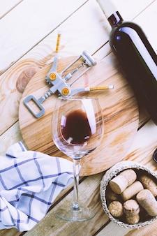 Fles wijn met wijnglas op wit hout