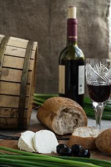 Fles wijn, olijven, kaas en brood staan op plundering