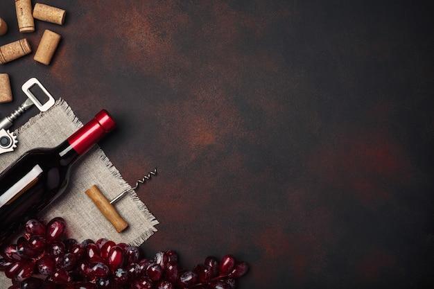 Fles wijn, rode druiven, kurkentrekker en kurken, op roestige achtergrond bovenaanzicht