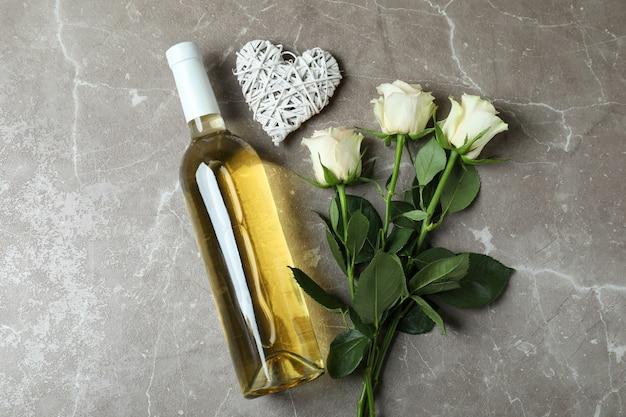Fles wijn, rozen en hart op grijze gestructureerde achtergrond
