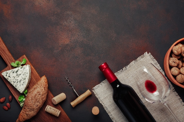 Fles wijn, walnoot, blauwe kaas, amandelen, kurkentrekker en kurken, op roestige achtergrond bovenaanzicht