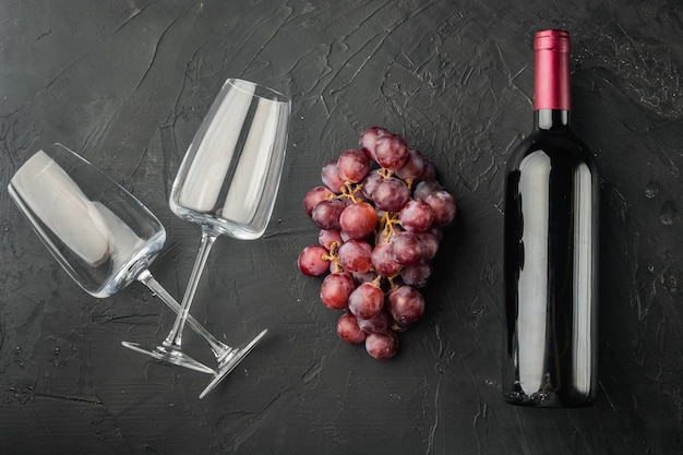 Fles wijn, wijnglazen, druiven set, op zwarte stenen tafel, bovenaanzicht plat lag
