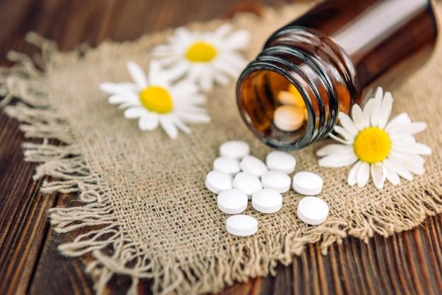 Fles witte kruidenpillen en kamillebloemen op donker hout, homeopathische geneeskunde.