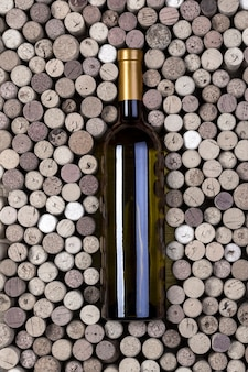 Fles witte wijn en kurken op houten tafel