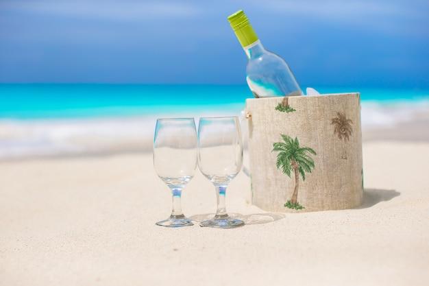 Fles witte wijn en twee glazen op het exotische zandstrand