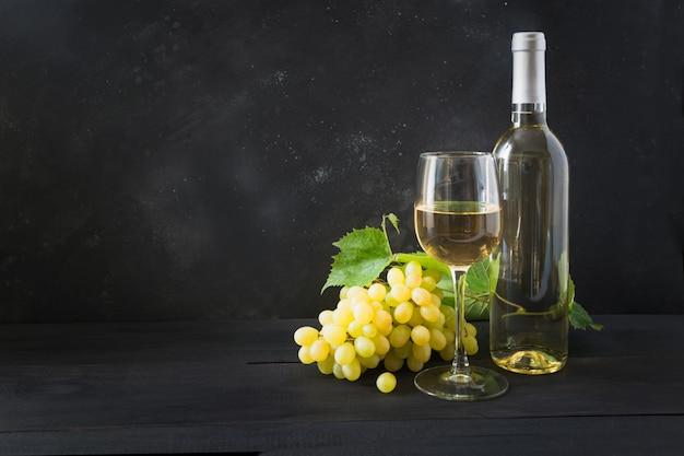 Fles witte wijn met wijnglas, rijpe druif op zwarte houten tafel.