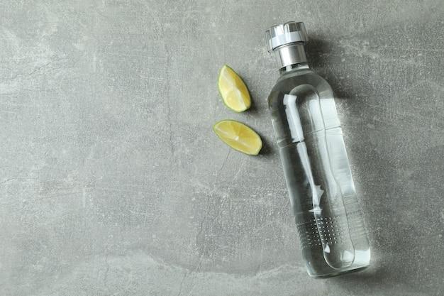 Fles wodka en limoenplakken op grijs
