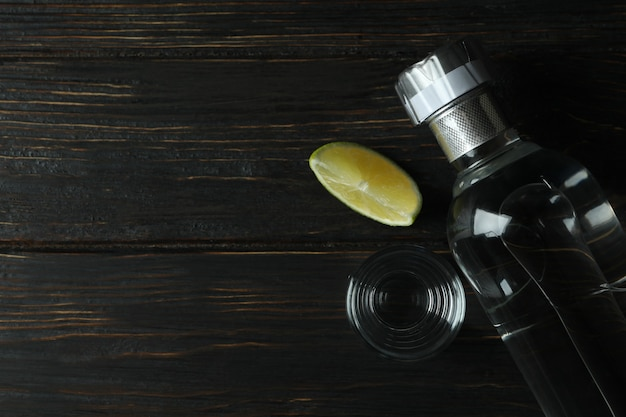 Fles wodka, schot en limoenplak op houten tafel
