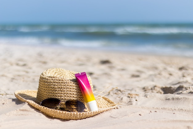 Fles zonnebrandcrème met zonnebril en hoed op strand