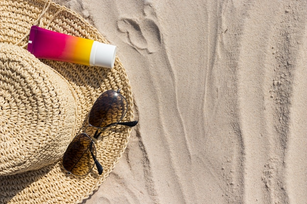 Fles zonnebrandcrème met zonnebril en panamhat op het strand, remedies voor de zomerhuid en bescherming