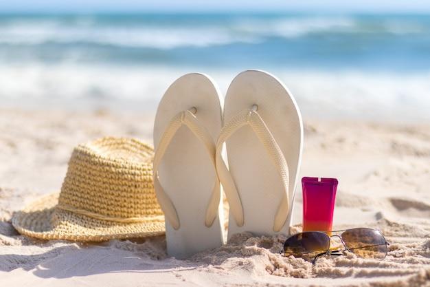 Fles zonnebrandcrème met zonnebril, panamhat en pantoffel op het strand, zomerse huidremedies en bescherming