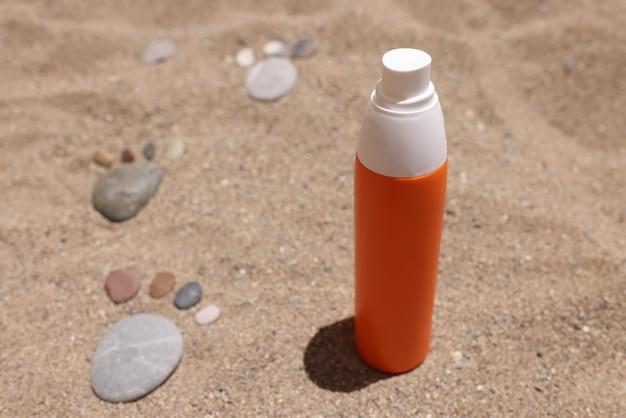Fles zonnebrandcrème zit op heet zand