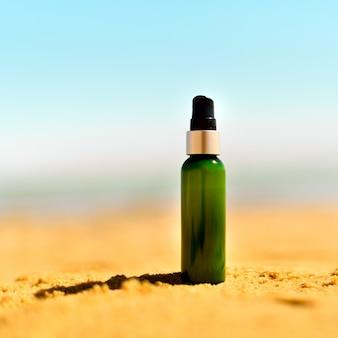 Fles zonnescherm in zand tegen overzeese achtergrond. vakantie en reizen behang. huidverzorging concept.