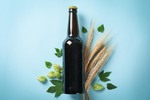 Flesje bier, tarwe en hop op blauwe tafel