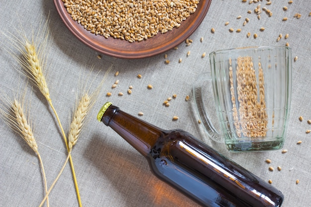 Flesje bier, tarwe, lege mok op zak.