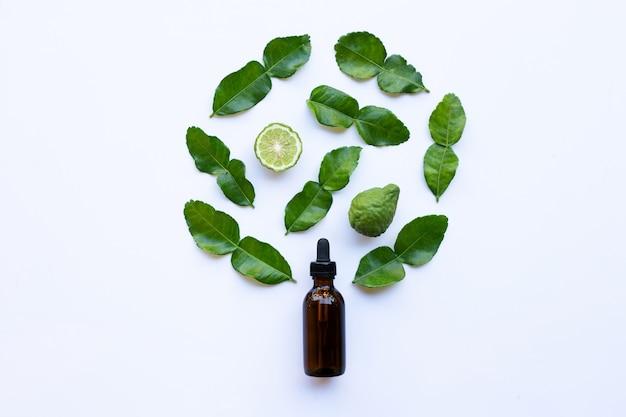 Flesje etherische olie en verse kaffir limoen of bergamot fruit met bladeren