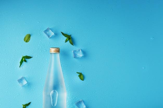 Flesje met een ijskoude drank, ijsblokjes, druppels en muntblaadjes