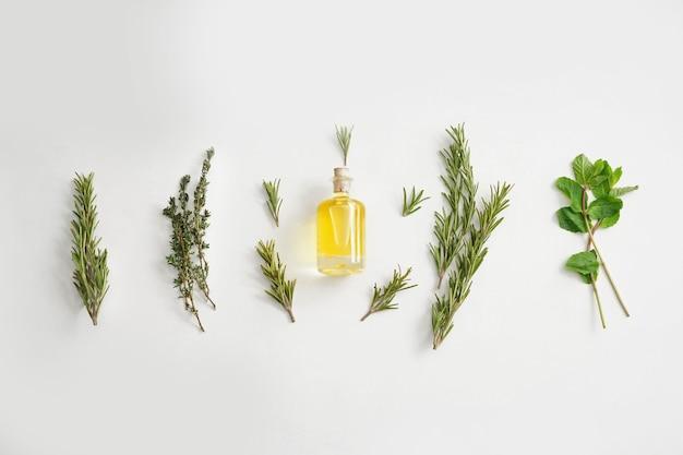 Flesje olie met verschillende kruiden op wit