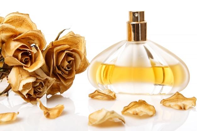 Flesje parfum en droge roze bloem