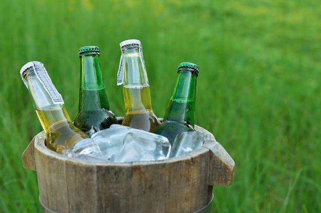 Flessen bier in houten emmer met ijs
