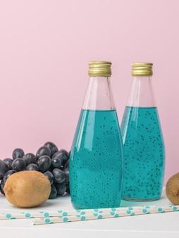 Flessen blauwe cocktail met basilicumzaden op een roze oppervlakte