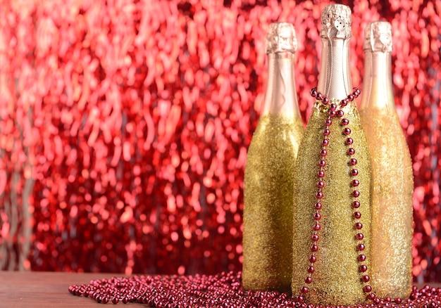 Flessen champagne met kerstversiering op lichte achtergrond