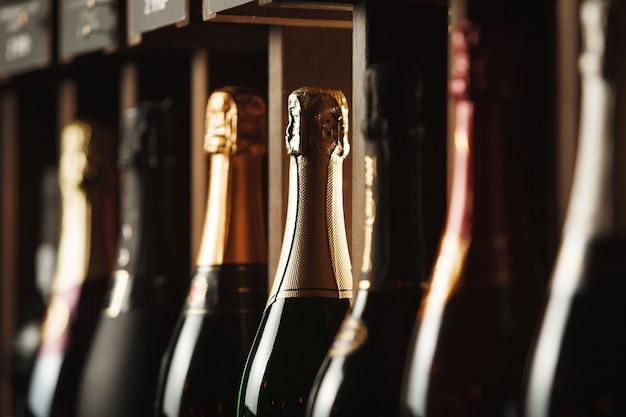 Flessen champagne op de plank close-up afbeelding van alcoholische dranken in de wijnkelder achtergrond met verschillende dure dranken