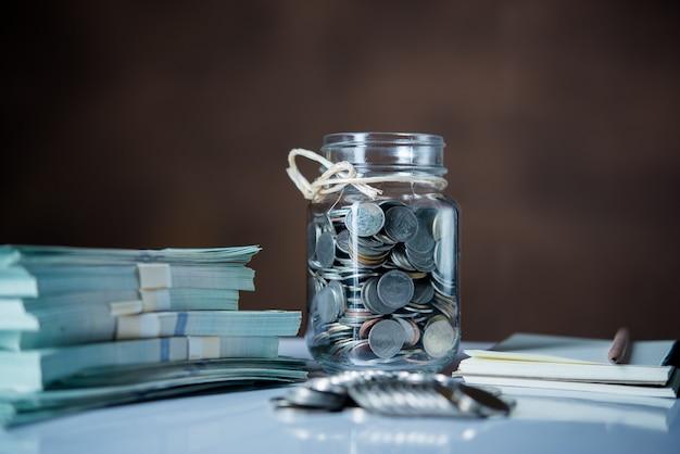 Flessen contant geld met muntstukken in het concept van het besparingsgeld