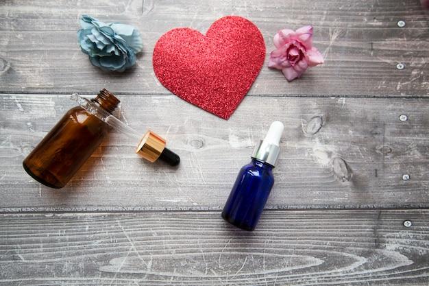 Flessen en een pipet met hyaluron serum voor cosmetische en cosmetische ingrepen op een houten ondergrond met bloemen