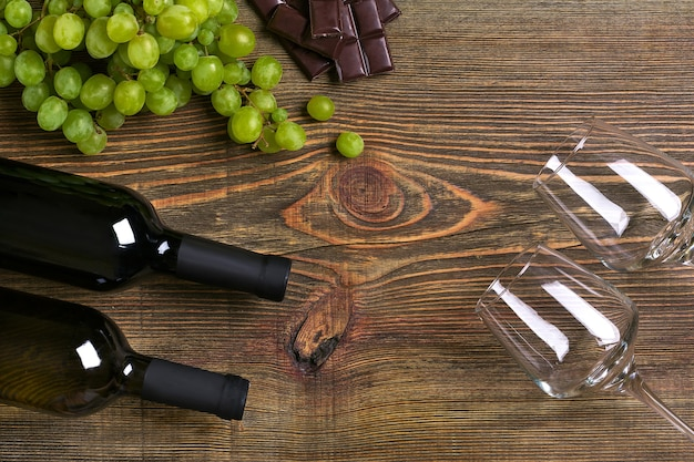 Flessen en glazen wijn, chocolade en rijpe druiven op houten achtergrond. bovenaanzicht. ruimte kopiëren. plat leggen. stilleven