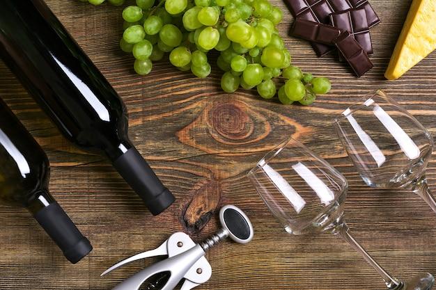 Flessen en glazen wijn, kaas en rijpe druiven op houten achtergrond. bovenaanzicht. ruimte kopiëren. plat leggen. stilleven