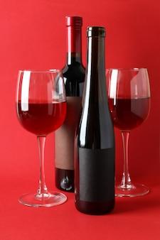 Flessen en glazen wijn op rode achtergrond