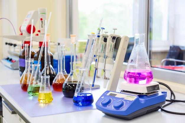 Flessen en schalen met gekleurde vloeibare reagentia in een wetenschappelijk laboratorium.