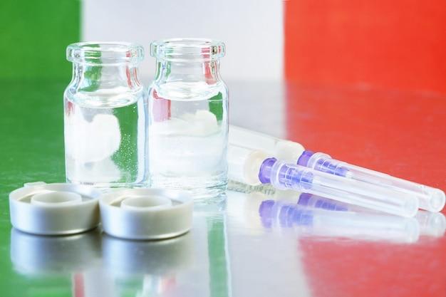Flessen en spuiten met vaccin tegen covid-19 op italiaanse vlag achtergrond, vaccinatie tegen coronavirus in italië begon concept, close-up