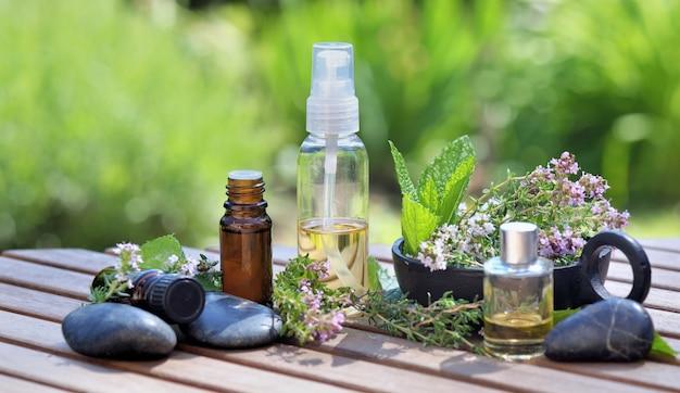 Flessen etherische oliën op een tafel met aromatische kruiden en zwarte stenen