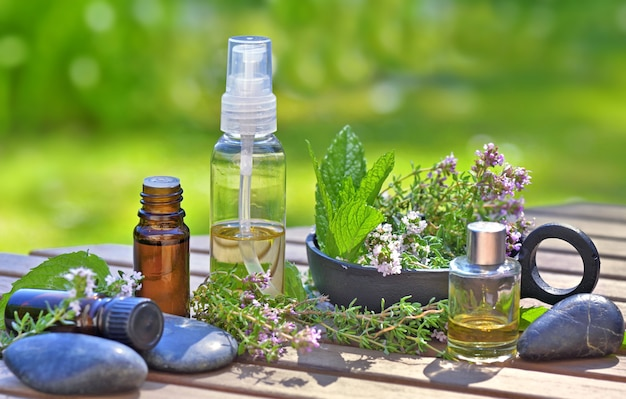 Flessen etherische oliën op een tafel met lavendelbloemen en muntblad in kom