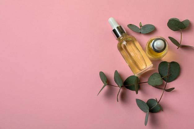 Flessen eucalyptusolie en twijgen op roze achtergrond