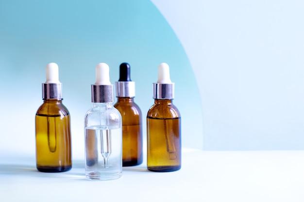 Flessen hyaluronzuur op een blauwe achtergrond die de vrouwelijke huid van het gezicht verzorgen