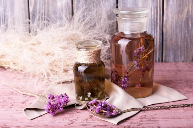 Flessen kruidentinctuur en brunch van bloemen op een servet op een houten tafel voor houten muur