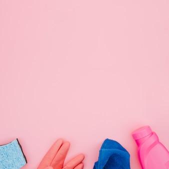 Flessen met afwasmiddel; handschoenen; blauw servet en sponzen op roze achtergrond