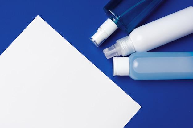 Flessen met antibacterieel handdesinfecterend middel op blauw met exemplaarruimte