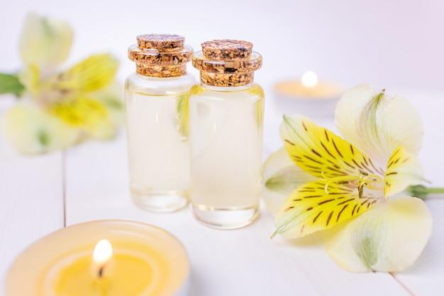 Flessen met bloemenetherische olie op een wit hout.