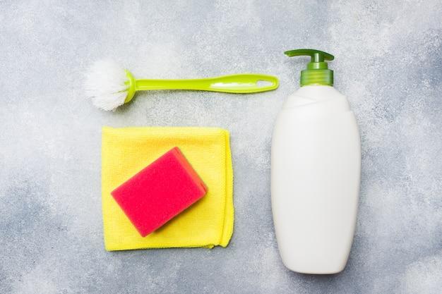 Flessen met detergentia, borstels en sponsen op concrete achtergrond.