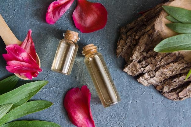 Flessen met essentie of olie met bloemblaadjes plat op een donkere ondergrond