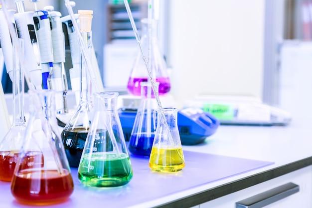 Flessen met gekleurde vloeibare reagentia in een wetenschappelijk laboratorium. blauw afgezwakt